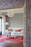 From the hallway, with its decorative wallpaper, French doors open into a spacious living room