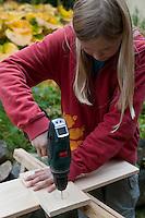 Mädchen baut einen Vogel-Nistkasten aus Brettern