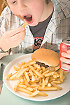 boy eats plateful of junk food, french fries, hamburger and soft drink