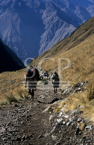 Inca Trail, Peru. View down Llulucha valley along trail with hikers carrying large packs coming up.