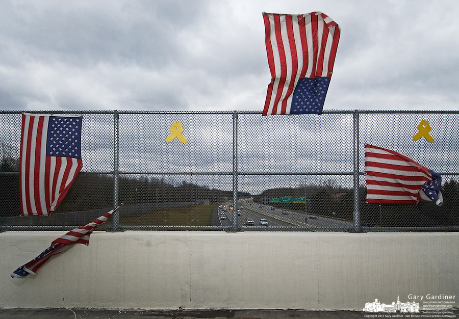 Flags displayed over an interstate highway are ripped from their anchors as a hard wind blows across the bridge Friday, Dec. 1, 2006.<br />