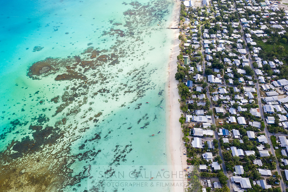 """An aerial view of downtown Funafuti, the capital of Tuvalu. Seen from above, it's easy to see why the Southwest Pacific country of Tuvalu has been identified as one of the world's most vulnerable nations to climate change. The country is made up of a collection of small islands and coral atolls, totalling only 27 square kilometres, scattered over 500,000 square kilometres of ocean. The highest point throughout the country is only 5 metres above sea level, resulting in special vulnerability to sea level rise. According to the Tuvaluan government, """"since 1993, sea level near Tuvalu has risen about 5mm per year; this is larger than the global average."""" Other challenges face the country including drought, ocean acidification and waste problems. Tuvalu. March, 2019."""