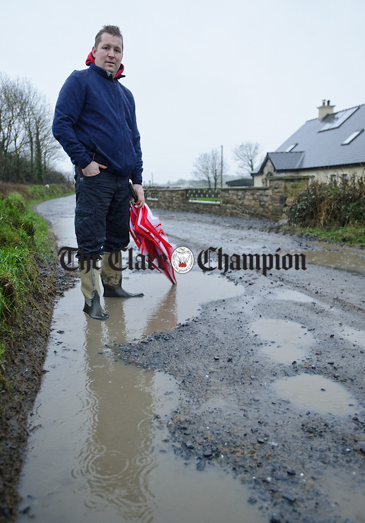 Brian Bermingham out on the pot-holed road outside his home at Cullenagh Labasheeda. Photograph by John Kelly.