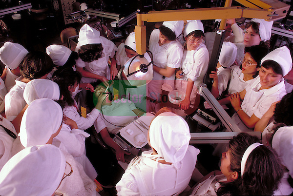 student dental technicians crowded around patient in chair during teaching demonstration