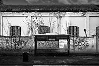 Milano, quartiere Bovisa, periferia nord. Una fermata ATM dell'autobus di fronte a un vecchio capannone industriale --- Milan, Bovisa district, north periphery. A bus stop in front of an old industrial shed