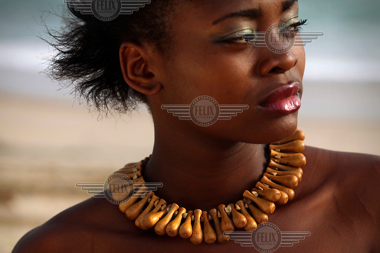 Model Kenny wears a necklace created by local fashion designer Bimpe Adebambo during a photo shoot on a Lagos beach.