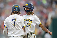 Michigan Wolverines outfielder Jordan Brewer (22) celebrates with teammate Jesse Franklin (7) after scoring against the Texas Tech Red Raiders during the first game of the NCAA College World Series on June 15, 2019 at TD Ameritrade Park in Omaha, Nebraska. Michigan defeated Texas Tech 5-3. (Andrew Woolley/Four Seam Images)