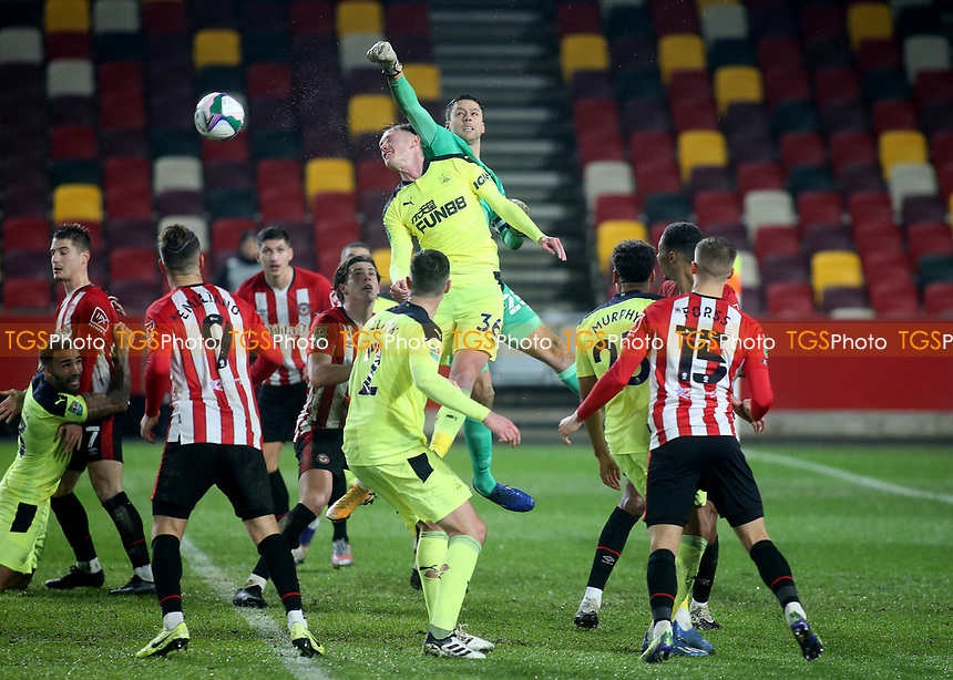 Brentford goalkeeper, Luke Daniels, punches the ball clear under pressure from Newcastle's Sean Longstaff during Brentford vs Newcastle United, Carabao Cup Football at the Brentford Community Stadium on 22nd December 2020