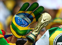 A massive Brazil hand touches a replica World Cup trophy