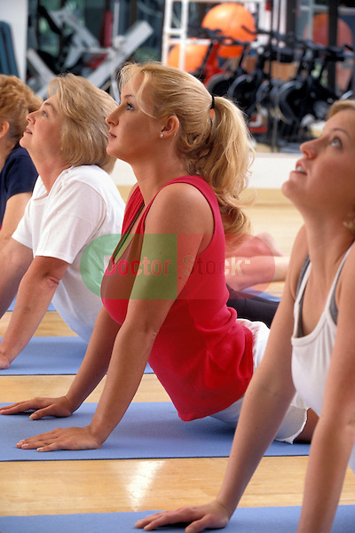 healthy young women and elderly woman enjoying aerobic workout in health club studio