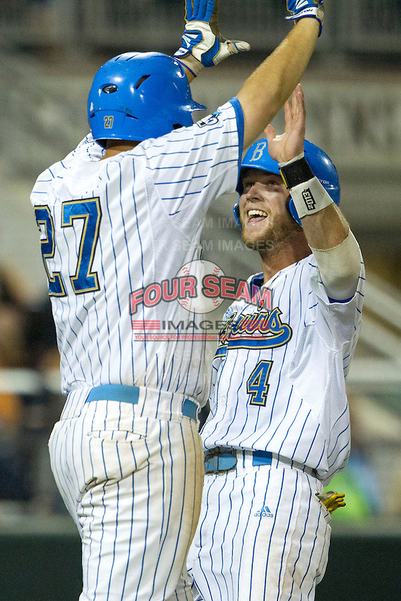 UCLA outfielder Eric Filia (4) celebrates with first baseman Pat Gallagher (27) as he scores a run during Game 12 of the 2013 Men's College World Series against the North Carolina Tar Heels on June 21, 2013 at TD Ameritrade Park in Omaha, Nebraska. The Bruins defeated the Tar Heels 4-1, to reach the CWS Final and eliminate North Carolina from the tournament. (Andrew Woolley/Four Seam Images)