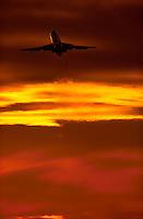A commercial jetliner takes off into a fiery orange sky as heat waves streak the sky.