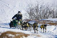 Jeff King runs up a hill onto the tundra from the Unalakleet river nearing Unalakleet