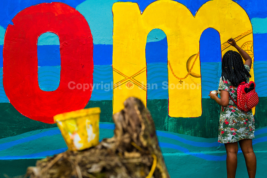 """An Afro-Colombian female student paints a society and environment-related mural on a school wall in Quibdó, Colombia, 5 October 2019. Supervised by a Bogotan street artist named Guache, a group of young activists from Chocó department created a large artwork called """"Somos Atrato"""" (""""We are [the river] Atrato"""") celebrating the Afro-Colombian heritage and accenting the inherent link between the communities and the river Atrato in the Pacific region of Colombia."""