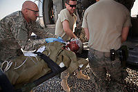 US Army soldiers load a wounded Afghan National Army (ANA) soldier onto a medevac helicopter manned by Charlie Company, Sixth Battalion, 101st Aviation Regiment medics and pilots near Kandahar.