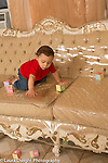 10 month old baby boy on couch throwing or dropping block, watching it fall