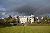 A rainbow streams down towards Goodwood House in an overcast sky
