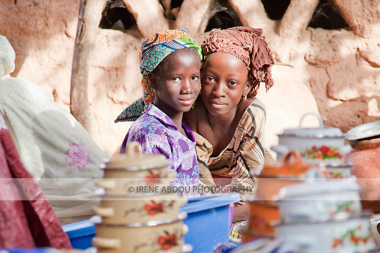 In the town of Djibo in northern Burkina Faso, a wedding has taken place.  Friends and family of the bride carry gifts and possessions of the bride - pots and pans, blankets, and textiles - from the bride's home to her new home with her husband.  Two girls peer over the pots and pans.