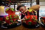 A Palestinian man carves watermelon on Eid congratulations on 3 august 2020. Photo by Osama Baba