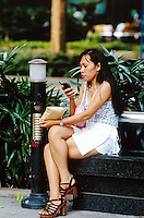 Singapore. Downtown. Town center. Orchard Road is mostly a place to shop with rows of modern shopping centres and the location for most international hotels. Philippino woman meet usually on sunday afternoon on Orchard road. A woman, wearing a mini skirt with high-heeled shoes and seated on a bench, uses her mobile phone to call her friends.  © 2001 Didier Ruef
