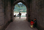 children and woman carrying basket at entry to village of ancient town Dachang along the Daning River, Lesser Three Gorges in rural China, Asia, 2003