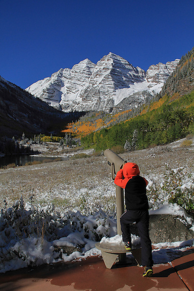 Boy using telescope, autumn at Maroon Bells, Aspen, Colorado. John offers fall foliage photo tours throughout Colorado.