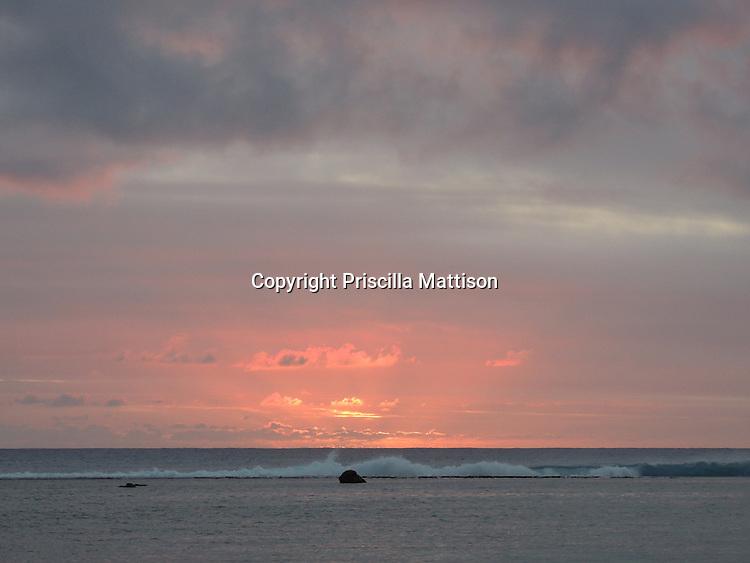 Rarotonga, Cook Islands - September 20, 2012:  A rosy glow lights up the sky over the lagoon.