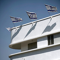 Israeli flags fly from the roof of a Bauhaus style building at 28 Rosh Pina Street built by architect Arieh Cohen in 1935. Tel Aviv is known as the White City in reference to its collection of 4,000 Bauhaus style buildings, the largest number in any city in the world. In 2003 the Bauhaus neighbourhoods of Tel Aviv were placed on the UNESCO World Heritage List. .