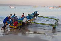 Jimbaran, Bali, Indonesia.  Fishermen Launching a Boat, Early Morning.