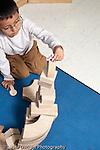 Education preschool 3-4 year olds block area boy building with wooden blocks vertical