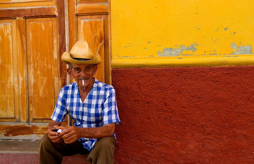 Portrait of old man cowboy with hat in front of yellow wall in Trinidad Cuba