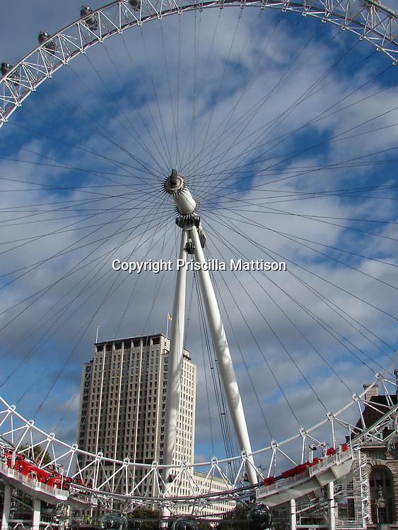 London, England - October 31, 2006:  The London Eye ferris wheel frames the urban backdrop and a vivid blue sky.