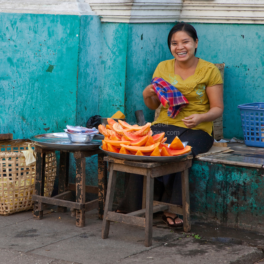 Myanmar, Burma, Yangon.  Street Food Vendor, Lady Selling Papaya.  She has a light coating of thanaka paste on her cheeks, as a cosmetic sunscreen.