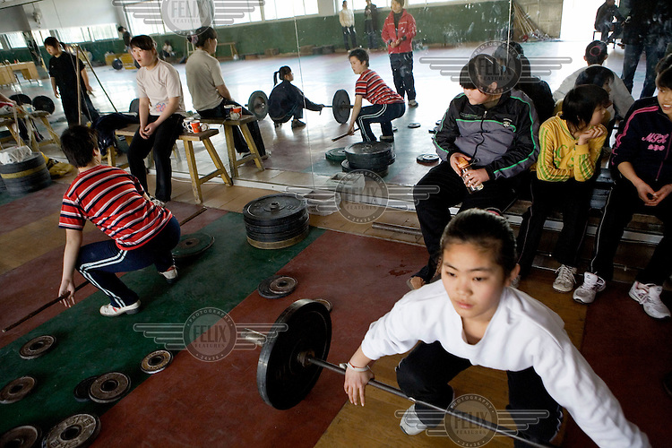 Students train at a weight-lifting class at the Weifang City Sports School, one of 3,000 state-run athletic academies that consign nearly 400,000 youngsters to a form of athletic servitude. In the category of weight-lifting, many of these students come from farming communities. They have been hand picked by sports scouts who travel to far away provinces visiting schools whilst taking detailed measurements of potential atheletes. There is more of a focus on finding girls as research by the Chinese state suggests that it is easier to win Olympic gold medals in this area. They measure shoulder width, thigh length and waist circumference - and if everything fits, these young students are told they have the honour of serving their motherland.
