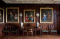 A set of portraits of young family members from the 18th century hang from a wall in the dining room