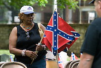 A Hilltop community resident collects Confederate flags after ceremonies at the Camp Chase Cemetery in Columbus, Ohio, Sunday, June 4, 2006. The Hilltop community association adopted maintenance of the Civil War cemetery and offers an annual memorial service honoring the more than 2,200 soldiers for the Confederacy and other Southern sympathizers buried in the small plot of land on the city's southeast side.<br />