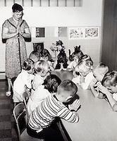 Children and teacher in prayer. 1950's.