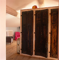 A cupboard with a old wooden louvre doors with a rustic, distressed finish.