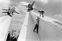 Russia. Krasnodar Krai Region. Krasnodar. City center. Turgeneva street. Two boys play on the concrete ramp of Mig-15 planes War memorial. The MiG-15 is a jet fighter aircraft of the Soviet Union. It was one of the first successful jet fighters to incorporate swept wings to achieve high transonic speeds. The MiG-15 is believed to have been one of the most produced jet aircraft. Krasnodar (also known as Kuban) is the largest city and the administrative centre of Krasnodar Krai in Southern Russia. 20.09.1993 © 1993 Didier Ruef