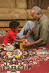 16 month old toddler baby boy playing with grandfather and shape sorter toy vertical