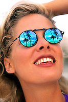 Beautiful woman with sunglasses and seeing reflection of vacation in palm trees and Caribbean
