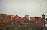 The Collioure village with the famous church Notre Dame des Anges, stone houses and red rooftops. A sailing boat on the Mediterranean sea., Languedoc-Roussillon, France. Grain grainy.