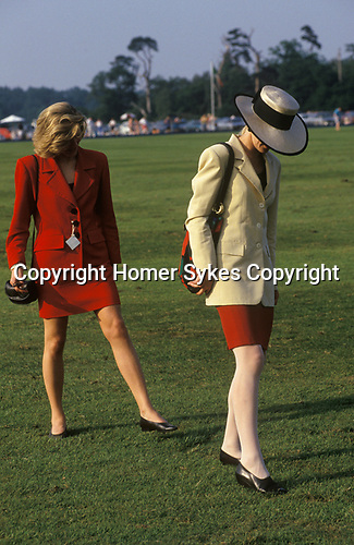Windsor, Berkshire. 1980's<br /> Dressed for the occasion and oh so chic at the Guards Polo Club, Smiths Lawn in Windsor Great Park. During a half time break in play, spectators are traditionally invited onto the pitch to stomp the divots. These are small patches of grass and dirt that have been torn up by the polo ponies' quick starts, stops and turns.