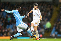 Bacary Sagna competes with Jack Cork during the Barclays Premier League Match between Manchester City and Swansea City played at the Etihad Stadium, Manchester on 12th December 2015