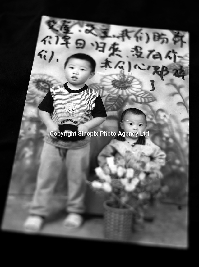 """Picture of two little boys who were stolen. Ai Jin (left), 5 years old and Ai Yu (right), 4 years old lost in GuanDu district in Kumming city on 11 September 2001. Mother's message reads """"Ai Jin, Ai Yu, we look forward you to coming back soon. Our hearts are broken without you.""""..PHOTO BY SINOPIX"""