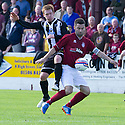 Linlithgow's Adam Nelson and Fraserburgh's Graham Johnston challenge for the ball .