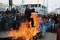 Turquie 2005   Célébration de Nowruz à Dogubayazit, la foule regarde un homme sauter au dessus du feu allumé dans la rue<br /> Turkey 2005    Nowruz in the street of Dogubayazit, the crowd looking  at a man jumping over the fire