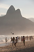 Rio de Janeiro, Brazil. Footballs in the air on Leblon beach with the Dois Irmaos mountain behind.