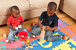 12 month old baby boy sitting on floor with toy blocks and container watching older brother age 3 playing game with toy animals horizontal learning by observation of older child