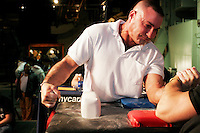 """Arm wrestlers compete at the 28th Annual Big Apple Grapple, held in New York City on March 19, 2005.  The tournament is the first in the 2005 New York Arm Wrestling Association's """"Golden Arm Series""""."""